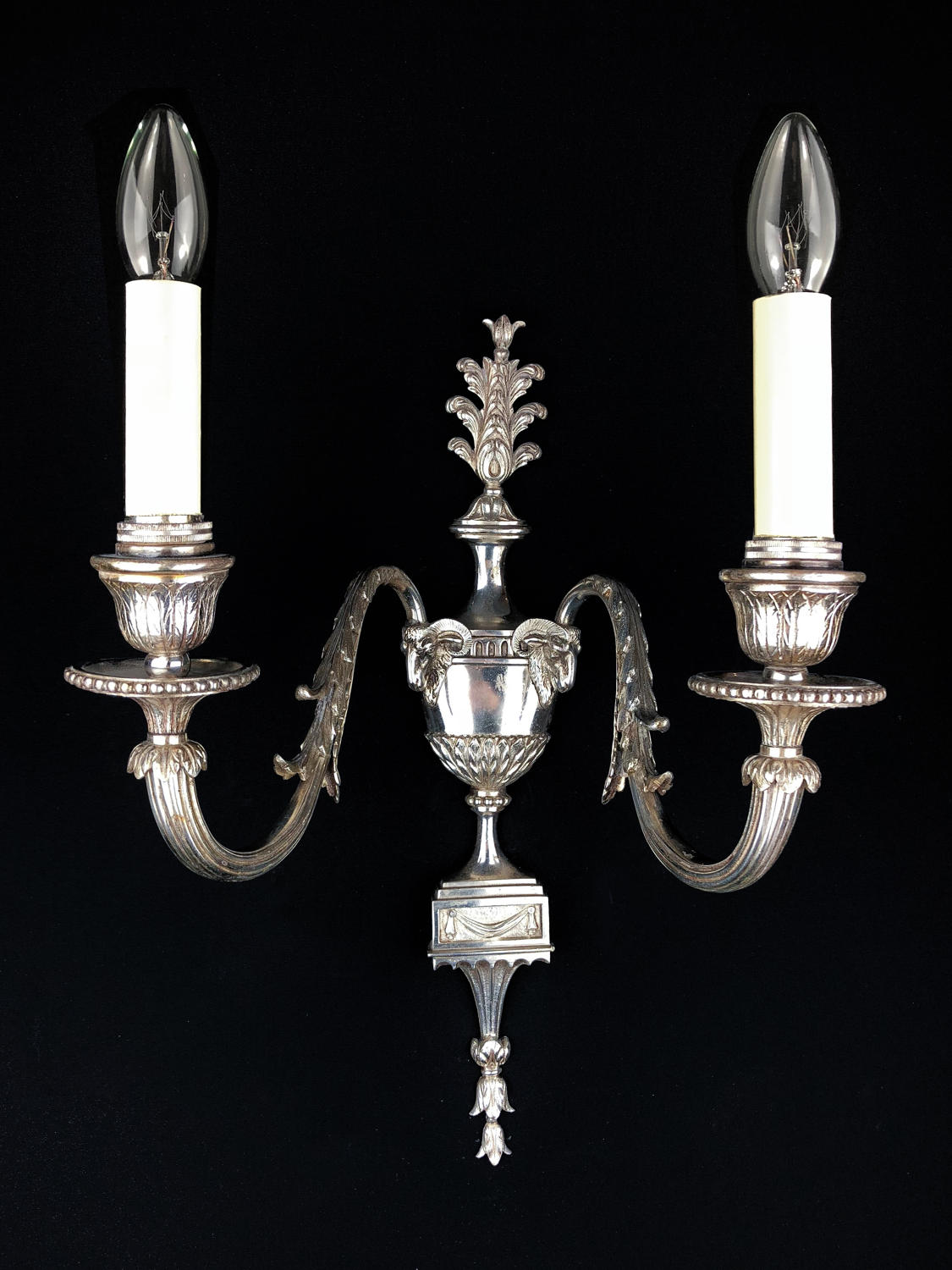 A single two arm silvered wall light