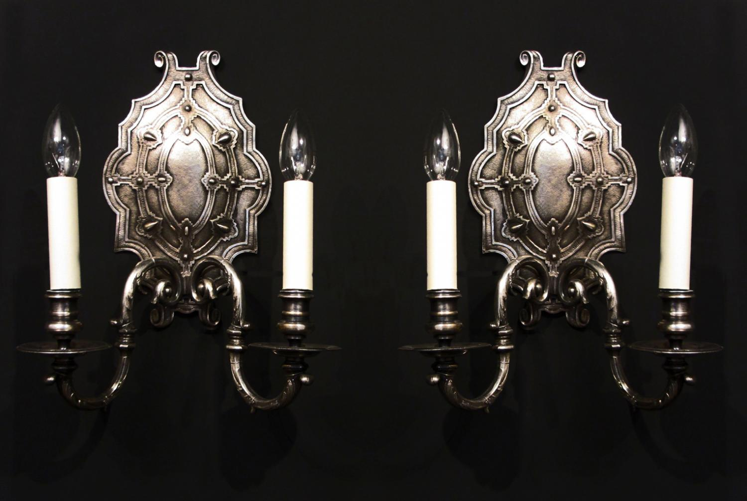 A pair of silvered two armed wall lights