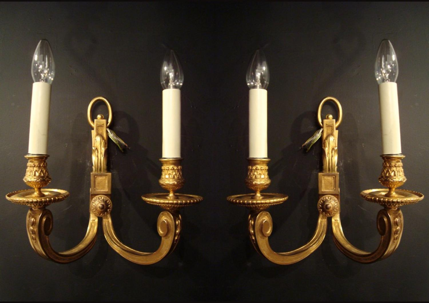 A pair of gilded bronze two armed wall lights