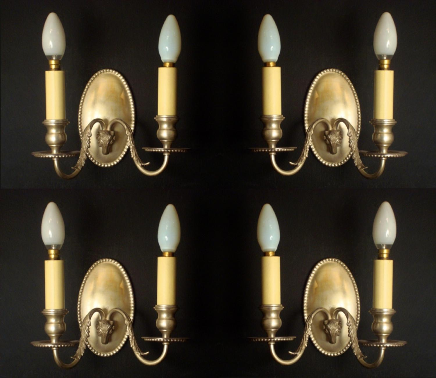 A set of 4 silvered brass two arm wall lights