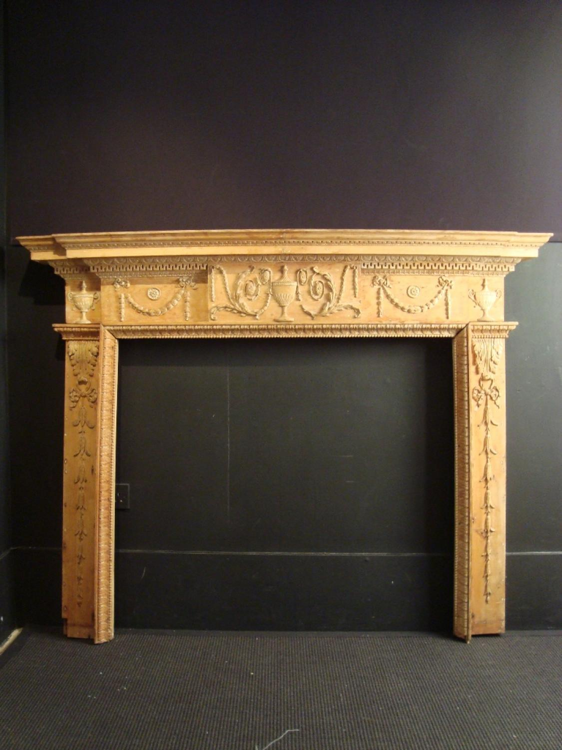 A George III carved pine fire surround