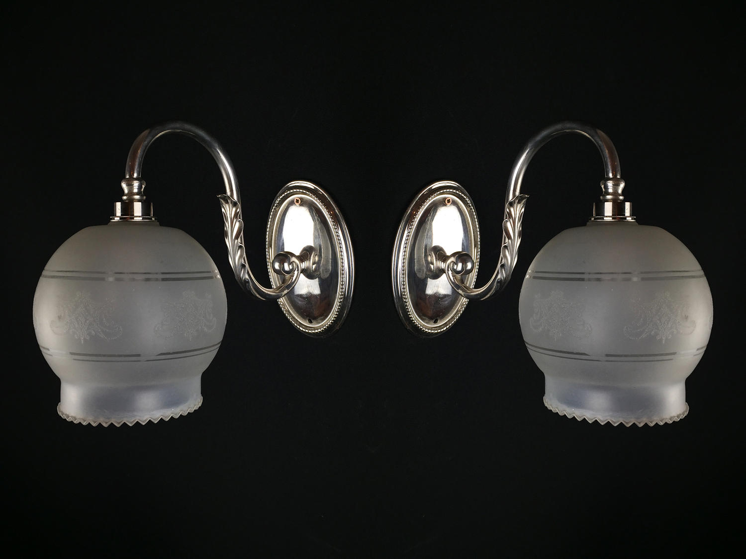 A pair of Edwardian silver plated single arm wall lights