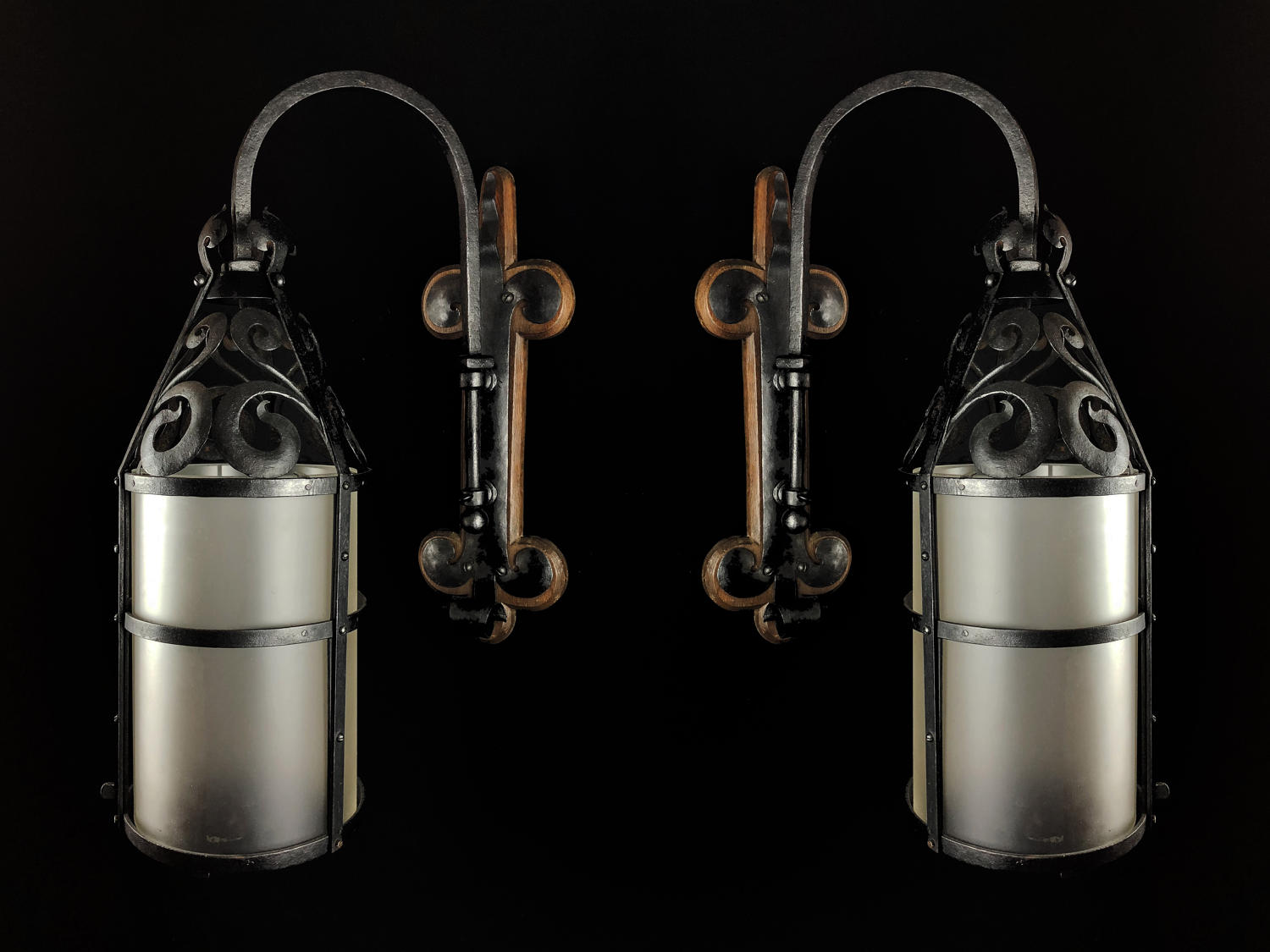 A pair of wrought iron wall lanterns