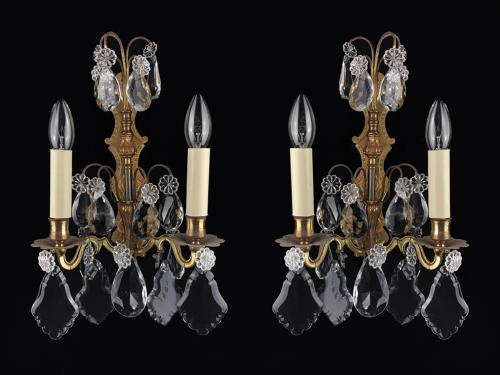 A pair of gilt and crystal wall lights