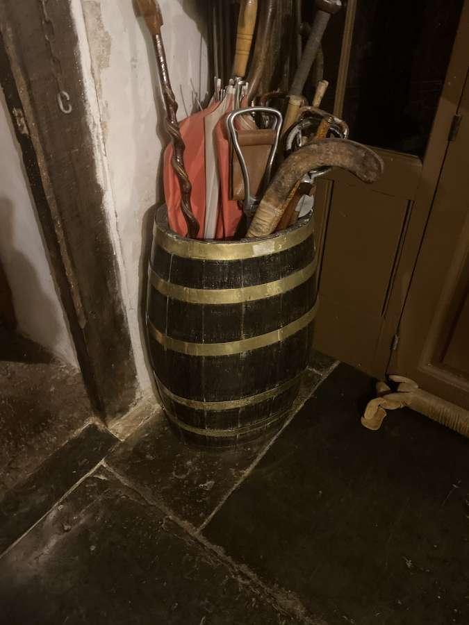 An oak umbrella stand with brass bindings