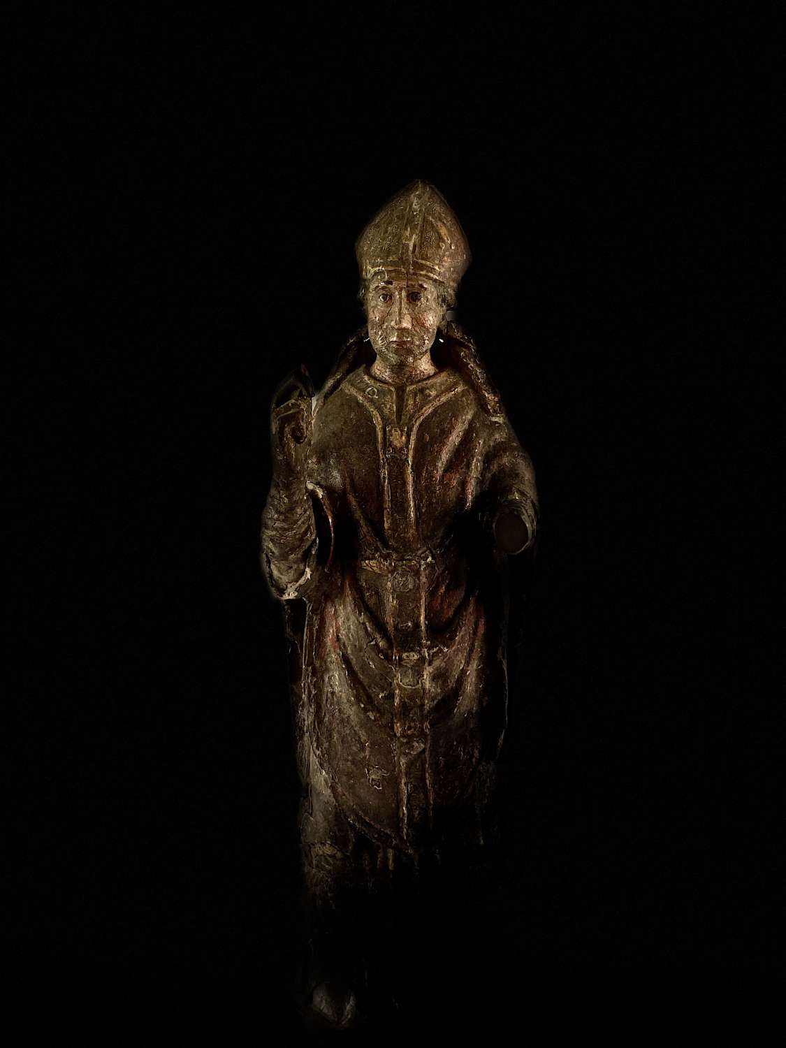A carved and polychrome figure of a bishop