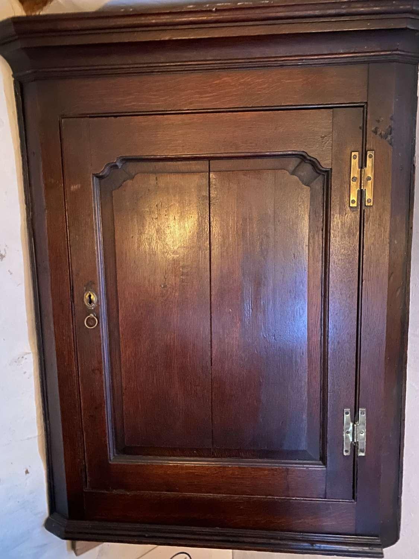An 18 century oak fielded panel corner cupboard